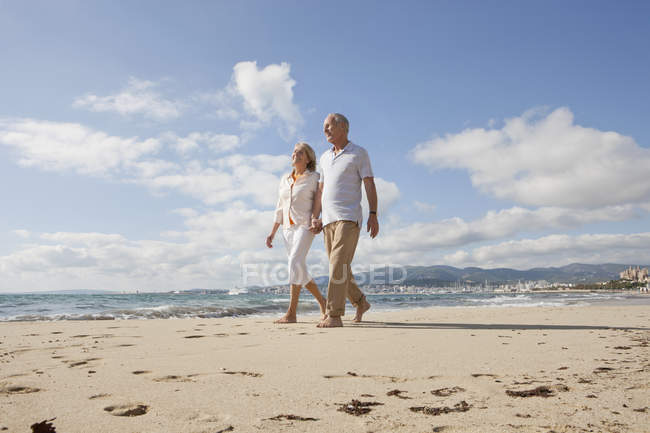 Senior couple walking along beach, smiling — Stock Photo