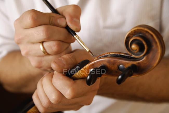 Craftsman painting handmade violin — Stock Photo