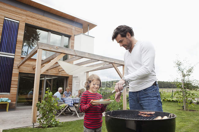 Father and son preparing food on barbecue, family sitting in background — Stock Photo