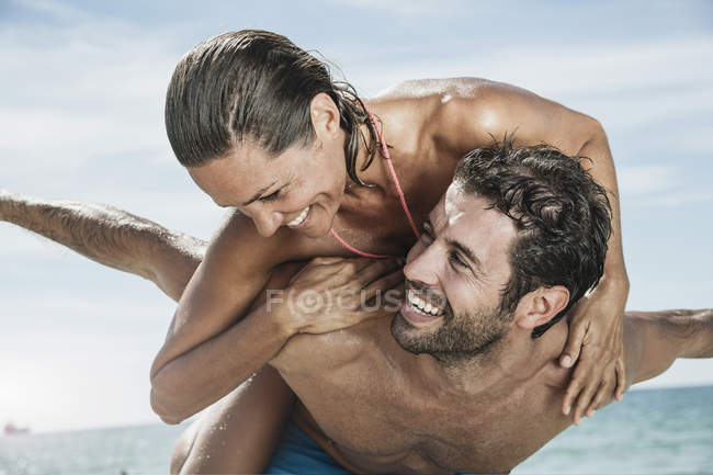 Mid adult man giving piggy back ride to woman — Stock Photo