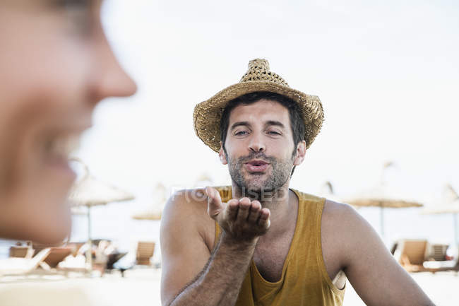 Mid adult man blowing kiss to woman — Stock Photo
