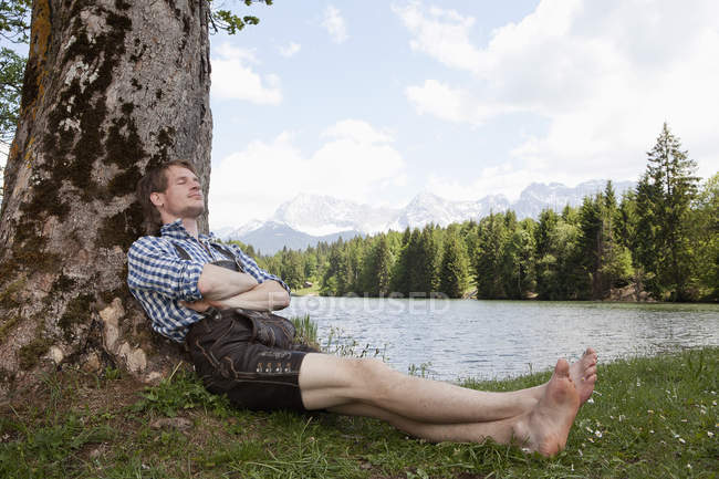 Germany, Bavaria, Mid adult man relaxing under tree — Stock Photo