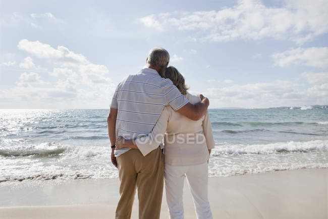 Senior couple looking at view on beach — Stock Photo