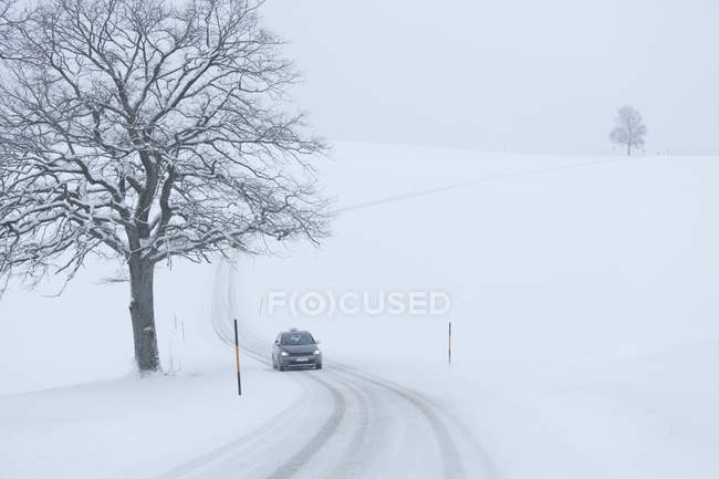 Car driving on snowy road in countryside — Stock Photo