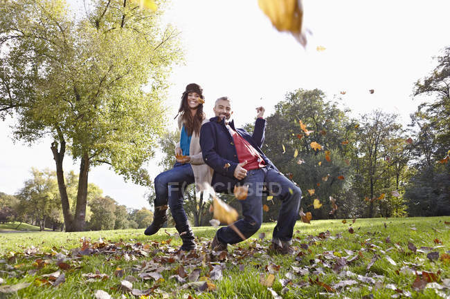 Couple playing in park, smiling, portrait — Stock Photo
