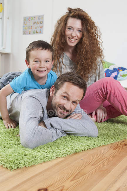 Smiling Family relaxing on floor and looking at camera — Stock Photo