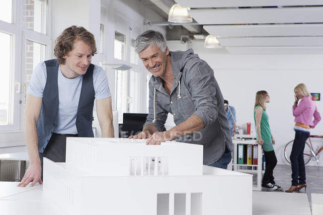 Men watching architectural model in office, colleagues talking in background — Stock Photo