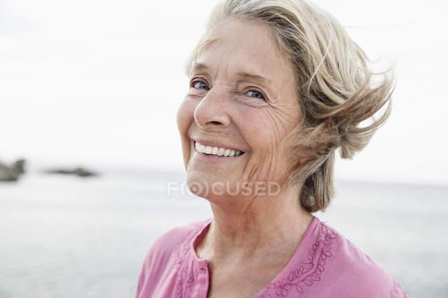 Senior woman smiling at Atlantic ocean — Stock Photo