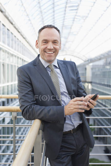 Businessman with cell phone, smiling, portrait — Stock Photo
