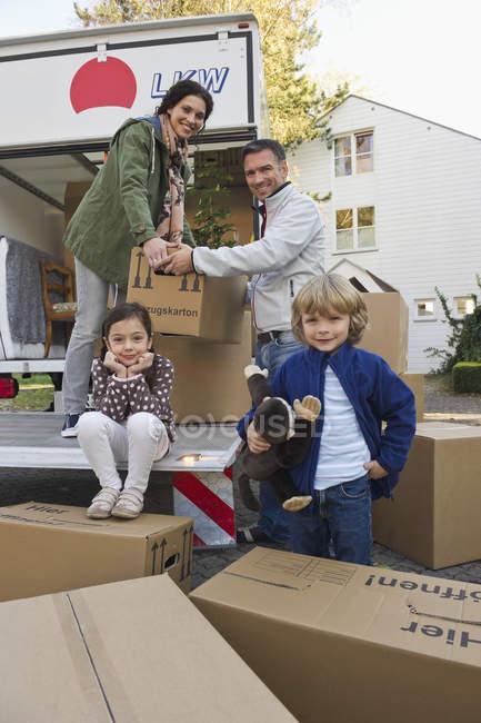 Famiglia con scatole di cartone per la casa mobile, concetto di casa mobile — Foto stock