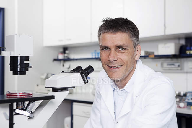 Scientist sitting with microscope in laboratory — Stock Photo