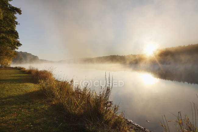 Misty Lake bei Sonnenaufgang — Stockfoto