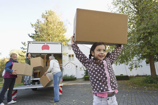 Family with cardboard box for moving house — Stock Photo