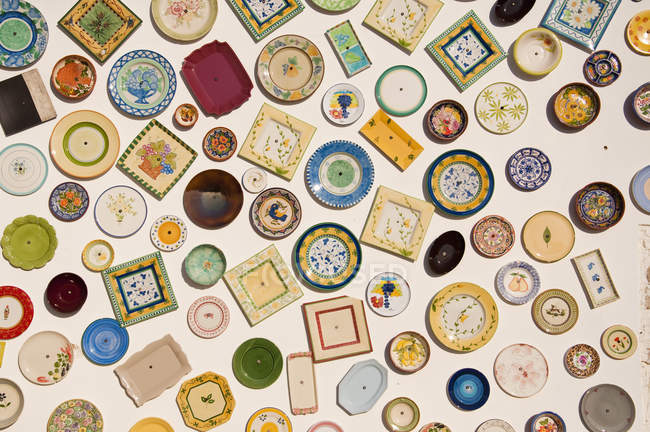 Variety of plates hanging on wall at pottery in Portugal — Stock Photo