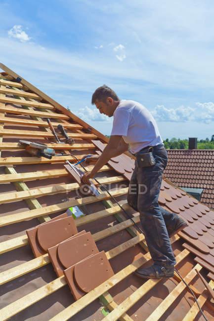 Metà uomo adulto misurazione tegola del tetto — Foto stock