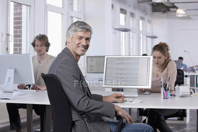 Mature man smiling with colleagues working in background — Stock Photo