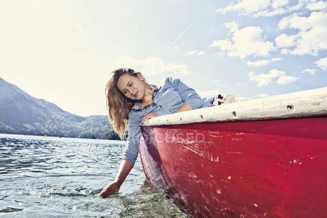 Young woman sitting in rowing boat, smiling — Stock Photo