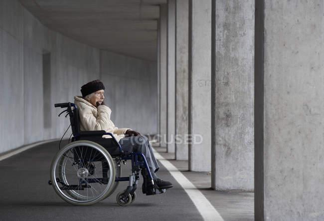 Старший женщина, сидя на инвалидной коляске — стоковое фото