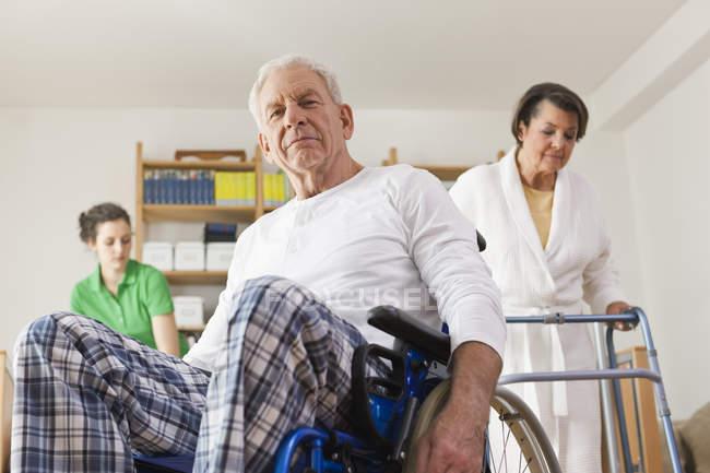 Senior man sitting on wheelchair, senior woman with walking frame — Stock Photo