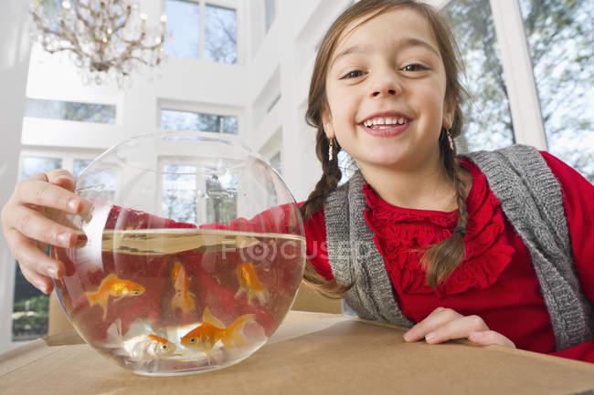 Ragazza con ciotola di pesce rosso, sorridente, concetto di casa in movimento — Foto stock