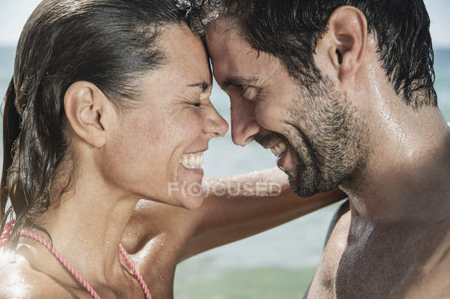Mid adult couple embracing, smiling face to face — Stock Photo