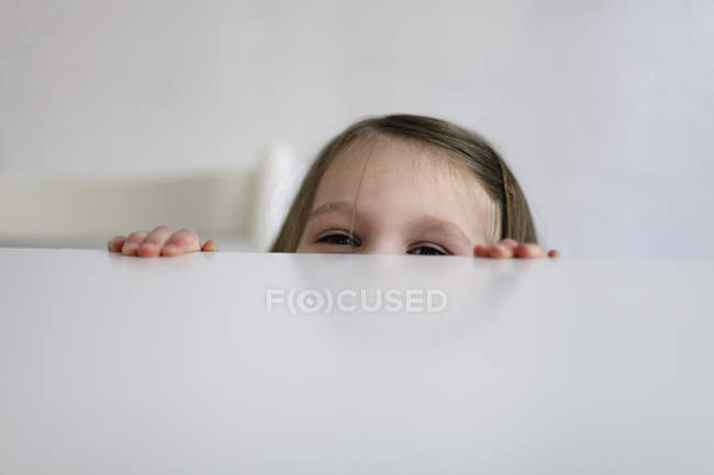 Close up of  Girl hiding at table — Stock Photo