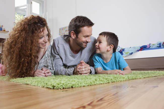Сім'я, весело на килим на дому — стокове фото