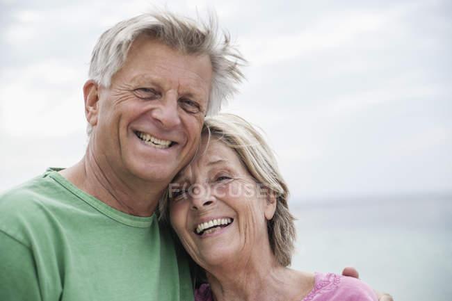Sorridente Coppia anziana in piedi sulla spiaggia testa a testa — Foto stock