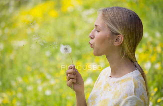 Portrait of teenage girl blowing blowball on a flower meadow — Stock Photo
