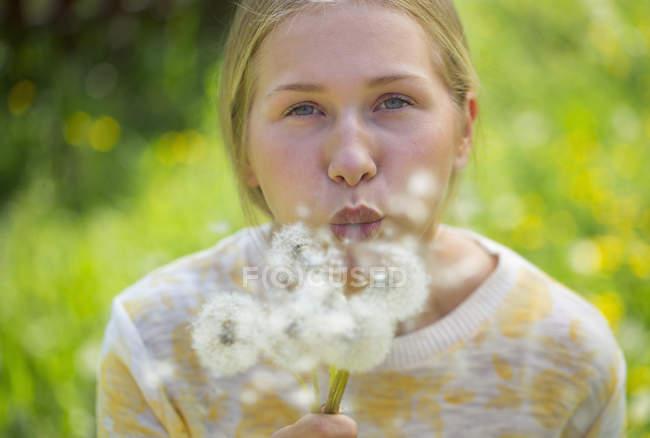 Portrait of teenage girl blowing blowballs on a flower meadow — Stock Photo