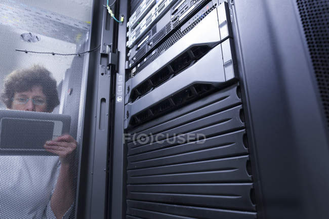Female technician with tablet computer standing in server room — Stock Photo