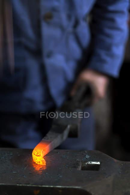 Germany, Bavaria, Josefsthal, blacksmith with glowing pickaroon at historic blacksmith's shop — Stock Photo