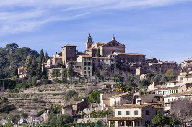 Ve a la aldea con la iglesia en la colina - foto de stock