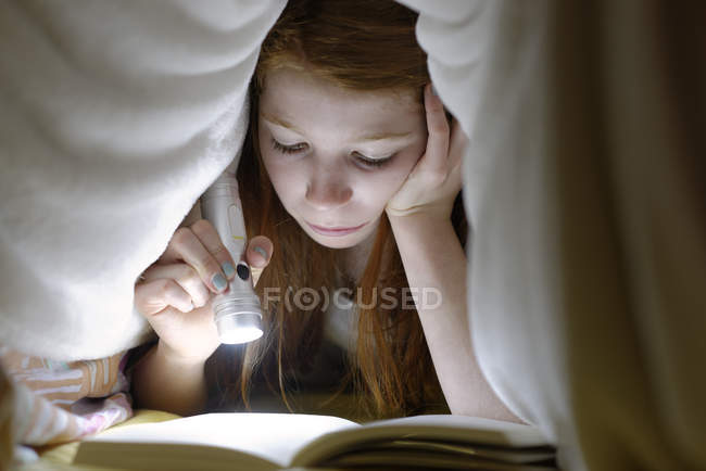 Portrait of girl reading a book secretly in bed under the blanket — Stock Photo