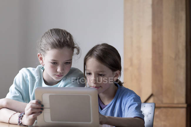 Brother and sister looking at tablet computer at home — Stock Photo