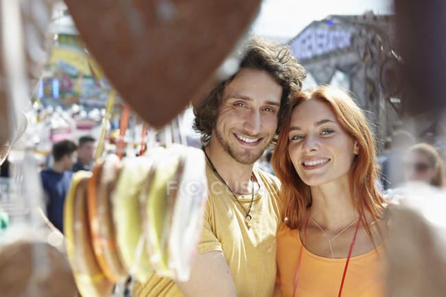 Портрет щасливі молода пара на парк атракціонів, пряників на передньому плані — стокове фото