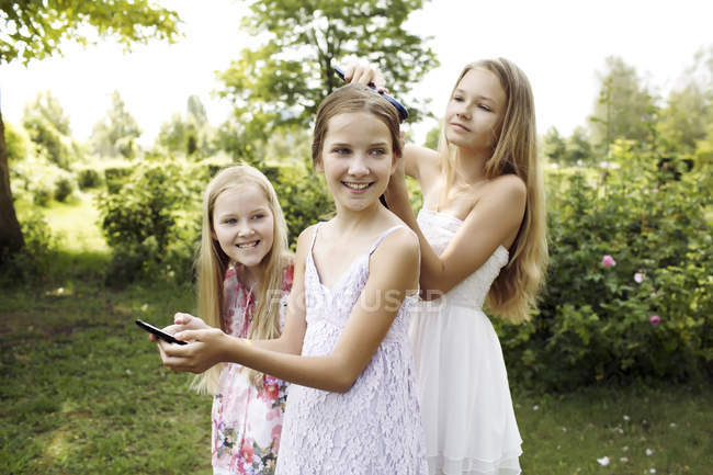 Three girls spending their time with hairdressing — Stock Photo