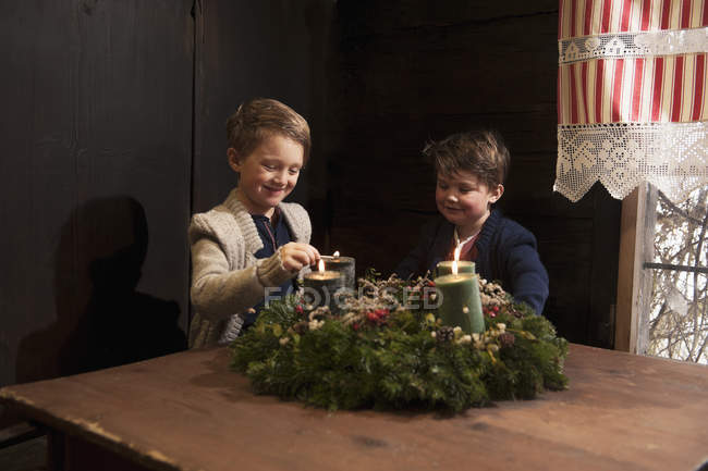 Two little boys lightning candles on a Advent wreath — Stock Photo