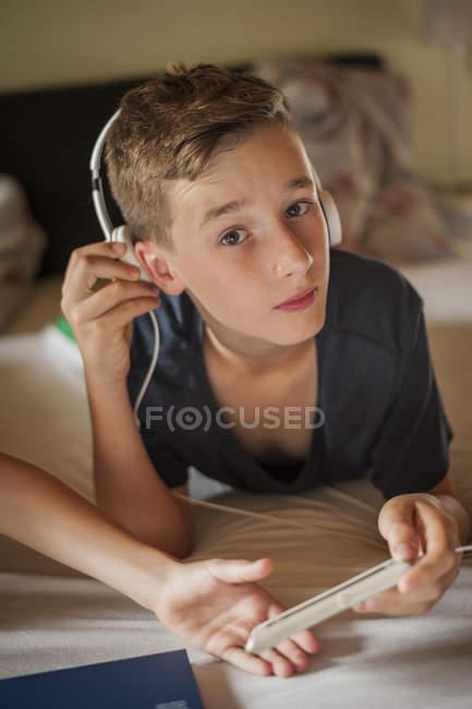 Boy lying on bed hearing music — Stock Photo