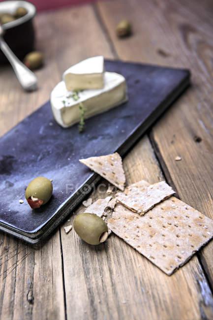 Piatto di formaggio e olive sul tagliere — Foto stock