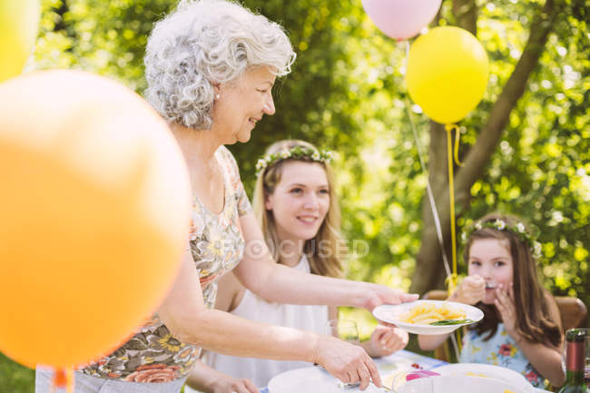 Grandmother serving daughter and granddaughter pasta on a garden party — Stock Photo