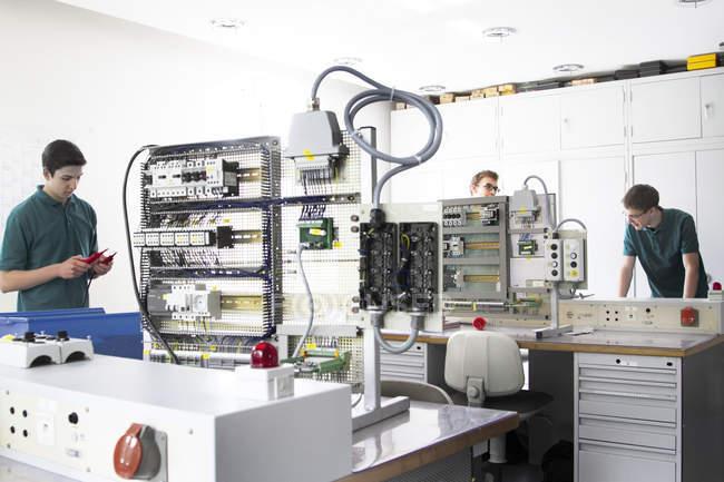 Trois apprentis électroniques debout en atelier — Photo de stock