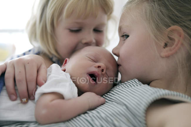 Two little girls kissing newborn brother — Stock Photo