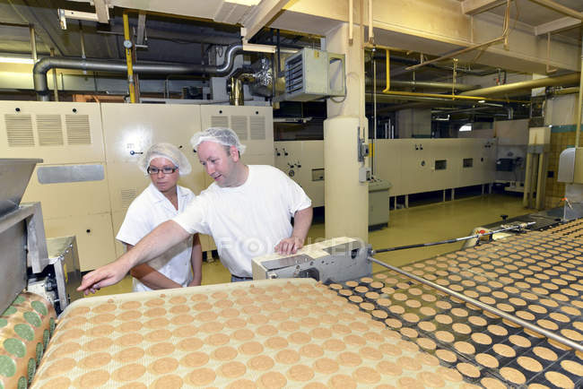 Two workers at production line with cookies in a baking factory — Stock Photo