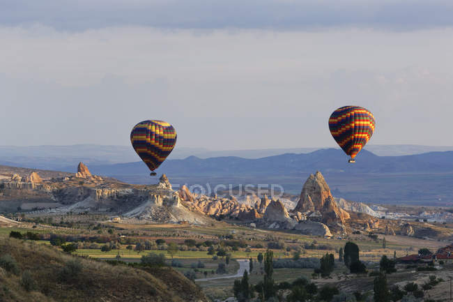 Turkey, Eastern Anatolia, Cappadocia, two hot air balloons hoovering over tuff rock formations at Goereme National Park — Stock Photo