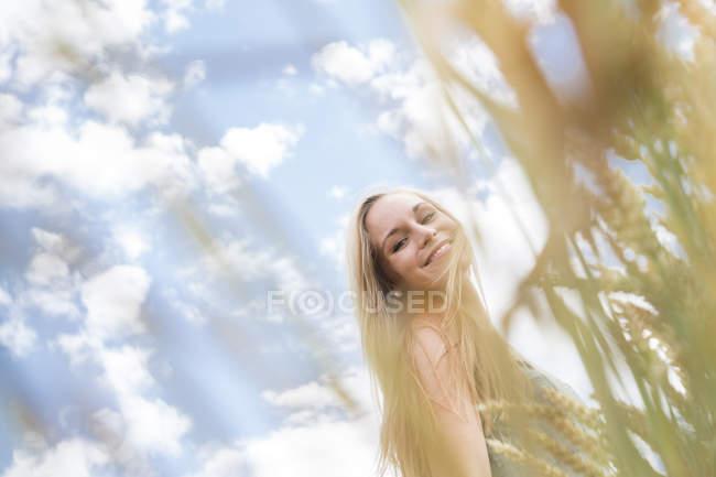 Портрет улыбающейся молодой женщины, стоящей на ржаном поле — стоковое фото