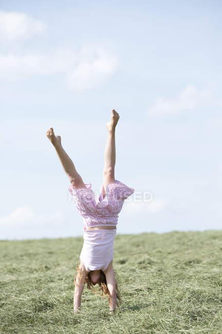 Junges Mädchen macht einen Handstand auf Wiese mit Heu — Stockfoto