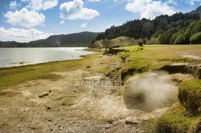 Portugal, Azores, Sao Miguel, Caldeiras at Lagoa das Furna and green grass shore against water — Stock Photo