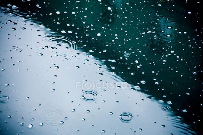 Краплі дощу падають на калюжу, частковим видом — стокове фото