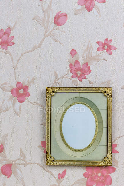 Empty picture frame on wallpaper with pink floral design — Stock Photo
